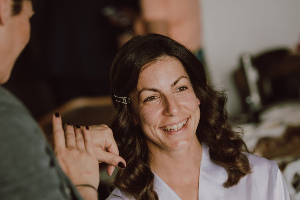 a beautiful smile on the bride's face as the makeup ends